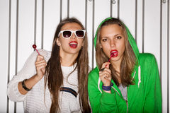Naughty girls. Portrait of two young naughty girls sucking lollipops, outdoors stock image