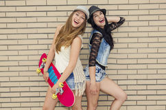 Naughty girls. Two beautiful and young girlfriends having fun with a skateboard, in front of a brick wall Stock Photo