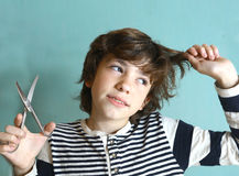 Naughty kid cut hair to himself with scissors Stock Photo