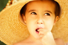 Naughty little boy in straw hat Stock Photography