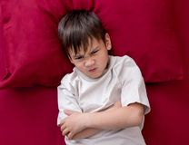 Naughty little boy won`t go to sleep. Naughty boy in white T-shirt laying on bed with arms under his head and won`t go to sleep Stock Images