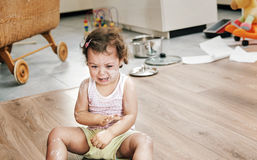 Naughty little child sitting on the floor Royalty Free Stock Image