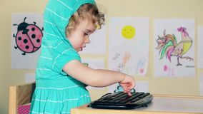 Naughty little girl child typing keyboard and talking with herself stock video