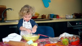 Naughty little girl clap hands with flour covered hands. mini chef in kitchen stock video footage