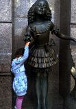 Naughty little girl and scolding statue. Naughty little girl wth the statue near to the Kyiv municipal puppet  theatre Royalty Free Stock Photo