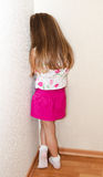 Naughty little girl is standing in the corner. At home Stock Images