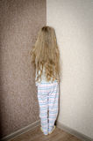 Naughty little girl is standing in the corner punished Stock Images