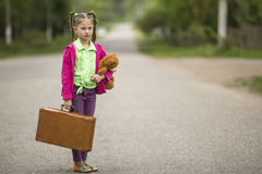 Naughty little girl with a suitcase and a Teddy bear is going on a trip. Travel. Royalty Free Stock Image