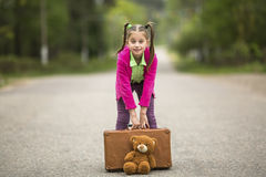 Naughty little girl with a suitcase and a Teddy bear is going on a trip. Walking. Royalty Free Stock Photography