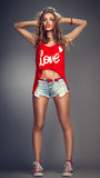 Naughty. A model female dressed in a red tank top, blue denim shorts and red keds,isolated on grey royalty free stock photo
