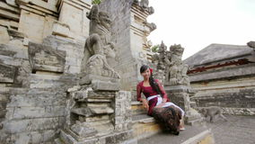 Naughty monkey try to steal from balinese girl, uluwatu temple stock video