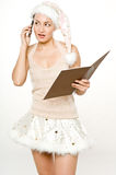 Naughty or Nice. A young female santa with her list and mobile phone Royalty Free Stock Photos
