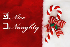 Naughty or Nice. A plush red stocking with a Candy Cane and words Nice and Naughty royalty free stock photography
