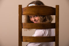 Naughty peep. Cute little girl peeping through the back of a chair Stock Images