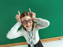 Naughty pupil making sassy funny expressions. Showing horns her hands. Photo of teen school girl wearing glasses, creative concept with Back to school theme Stock Photos