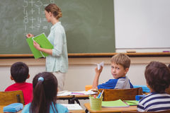Naughty pupil about to throw paper airplane in class Stock Image