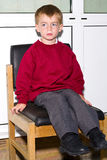 Naughty School boy. School boy in uniform sitting waiting expectantly Royalty Free Stock Images