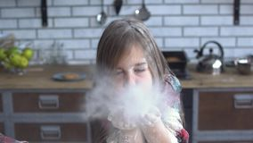 Naughty small girl rub her body and cloth with flour, kid blow away flour from her arms. Naughty cute small girl rub her body and cloth with flour, kid blow away stock footage