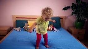 Naughty toddler girl jumping and falling on bedroom stock video