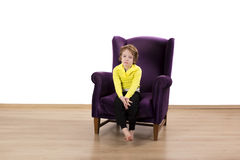 Naughty toddler time out punishment bored. Bored red hair boy sitting on the purple couch isolated on white background Stock Photos