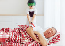 Naughty yelling grandson waking grandpa up by playing around in loud, noisy games. Naughty yelling grandson, kid waking grandpa up by playing around in loud Royalty Free Stock Images