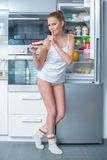 Naughty young woman stealing cake from the fridge Royalty Free Stock Image