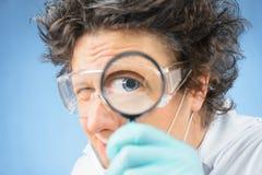 Naukowów spojrzenia przez powiększać - szkło obrazy stock