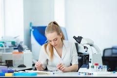 Naukowa badacz u?ywa mikroskop w laboratorium Medyczna opieki zdrowotnej technologia i ?rodka farmaceutycznego badanie i fotografia stock