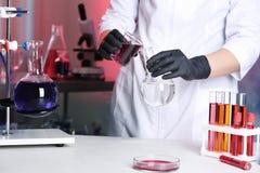 Naukowa dolewania odczynnik w kolbę przy stołem w laboratorium zdjęcia royalty free