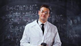 Naukowa mężczyzna w białym praca kontuszu blisko kredowej deski z równaniami pije kawę zdjęcie wideo