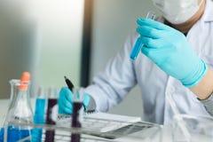 Naukowa nagranie robi notatce na książce z jego znalezienie próbną tubką w lab obrazy royalty free