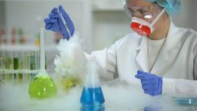 Naukowiec bierze żółtą ciekłą próbkę w pipecie i sprawdza cedziny, benzyna zbiory wideo
