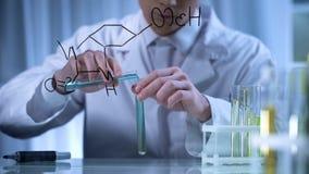 Naukowiec miesza substancje w próbnych tubkach według formuły pisać na szkle zdjęcie stock
