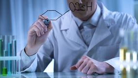 Naukowiec pisze chemicznej formule na przejrzystej desce, środka farmaceutycznego badanie zdjęcia royalty free