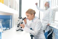 Naukowiec pracuje z mikroskopem podczas gdy jej kolega patrzeje kolbę behind w chemicznym laboratorium Obrazy Royalty Free