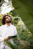 Naukowiec sprawdza rośliny przy szklarnią Fotografia Stock