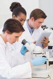 Naukowowie używa mikroskopu i pastylki komputer osobistego obrazy stock