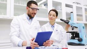 Naukowowie z pastylka komputerem osobistym i mikroskop w lab zbiory