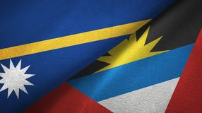 Nauru and Antigua and Barbuda two flags textile cloth, fabric texture. Nauru and Antigua and Barbuda two folded flags together royalty free stock photo