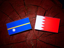 Nauru flag with Bahraini flag on a tree stump isolated Royalty Free Stock Photos