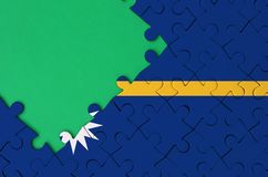 Nauru flag is depicted on a completed jigsaw puzzle with free green copy space on the left side.  stock images