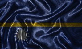 Wallpaper by Nauru flag and waving flag by fabric. royalty free stock photos
