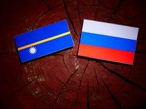 Nauru flag with Russian flag on a tree stump  Royalty Free Stock Photos