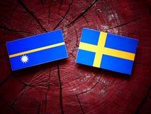 Nauru flag with Swedish flag on a tree stump  Royalty Free Stock Photos