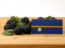 Nauru flag on a wooden panel with blackberries isolated on a whi Stock Photos