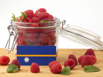 Nauru flag on a wooden panel with raspberries isolated on a whit Stock Photography