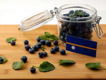 Nauru flag on a wooden plank with blueberries  on white Royalty Free Stock Images