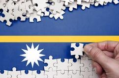 Nauru flaga przedstawia na stole na którym składa łamigłówkę biały kolor ludzka ręka zdjęcia royalty free