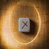 Nauthiz. Handmade scandinavian wooden runes on a wooden vintage background in a circle of light. Concept of fortune royalty free stock photography