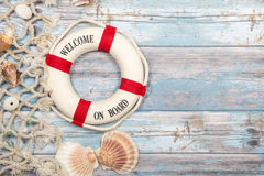 Nautica background with safety buoy with the text welcome on board seashells and fishing net on a blue scaffolding wooden backgrou. Nautica background with a red Stock Photo